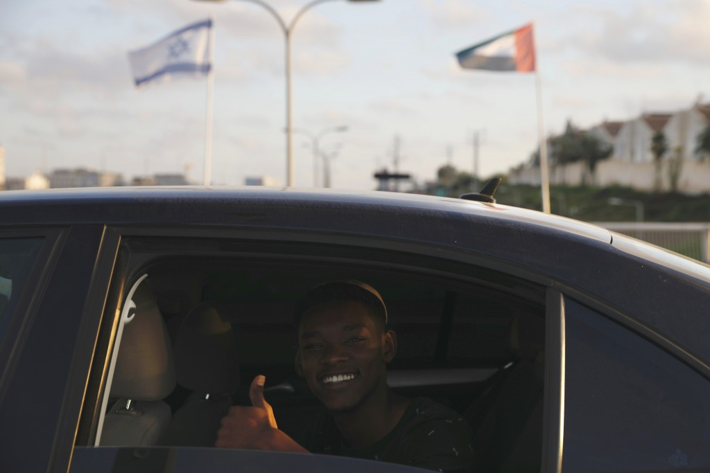 A man gives a thumbs up as he passes United Arab Emirates and Israeli flags at the Peace Bridge in Netanya, Israel, Sunday, Aug. 16, 2020. The UAE fla...