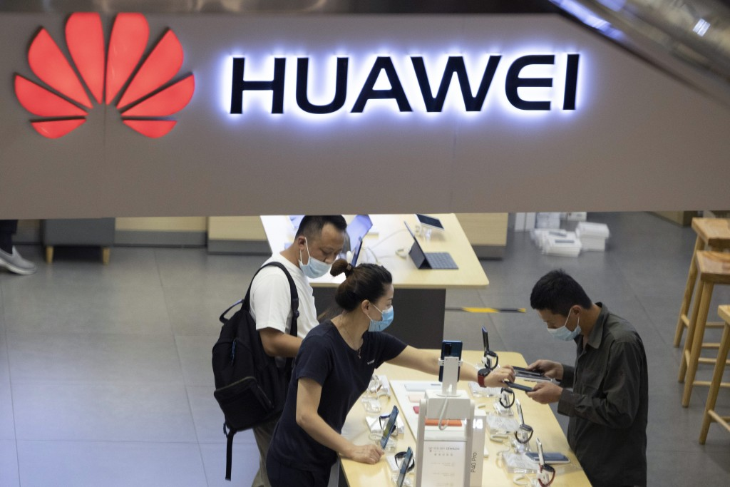 FILE - In this July 15, 2020, file photo, visitors wearing masks to curb the spread of the coronavirus look at the latest products at a Huawei store i...