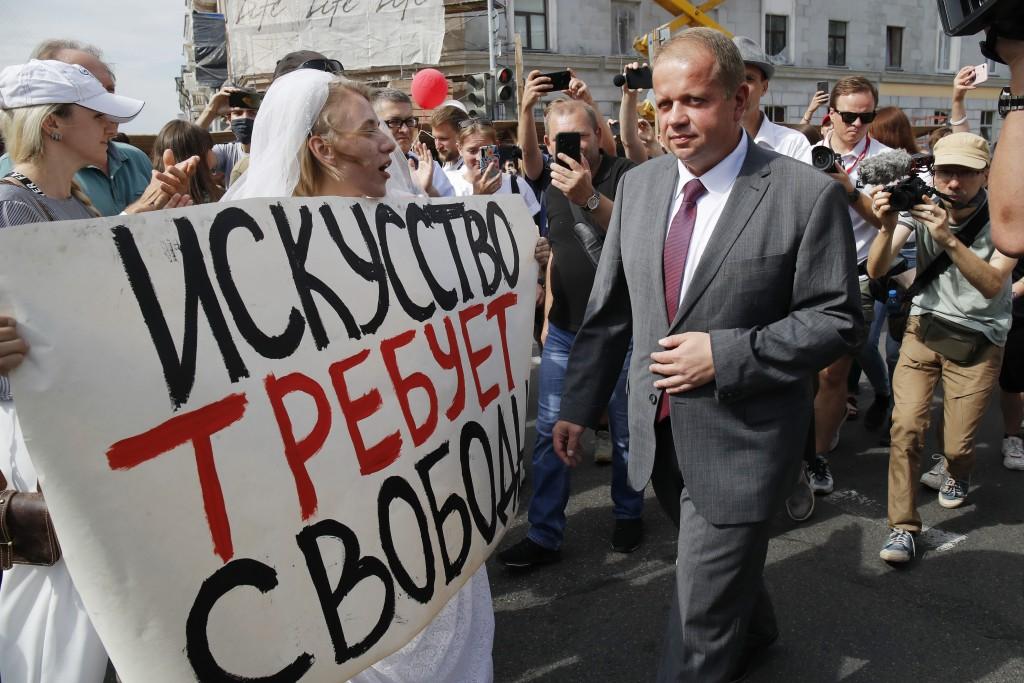 "Yuri Bondar, Belarusian Minister of Culture, passes a woman holding a banner reading ""Art demands freedom"" in Minsk, Belarus, Tuesday, Aug. 18, 2020. ..."