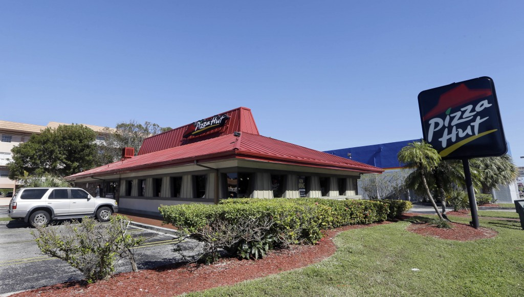 FILE- This Jan. 24, 2017, file photo shows a Pizza Hut in Miami. Pizza Hut has reached an agreement with one of its largest franchisees to close 300 u...
