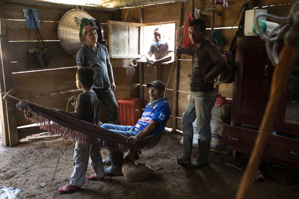 Residents gather inside a house days after it was partially burned by unidentified, armed men, on a coffee plantation in Cubilguitz, Guatemala, Tuesda...