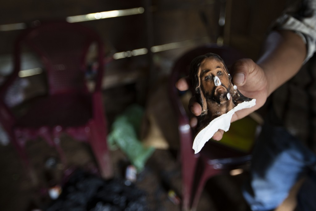 Julio Cesar Bol shows the head of a statue of Jesus that was decapitated during an attack inside his home that was partially burned by unidentified, a...
