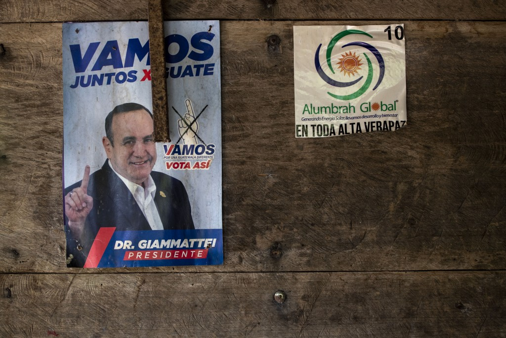 A campaign poster promoting current Guatemalan President Alejandro Giammattei hangs on a home that was partially burned by unidentified, armed men, on...