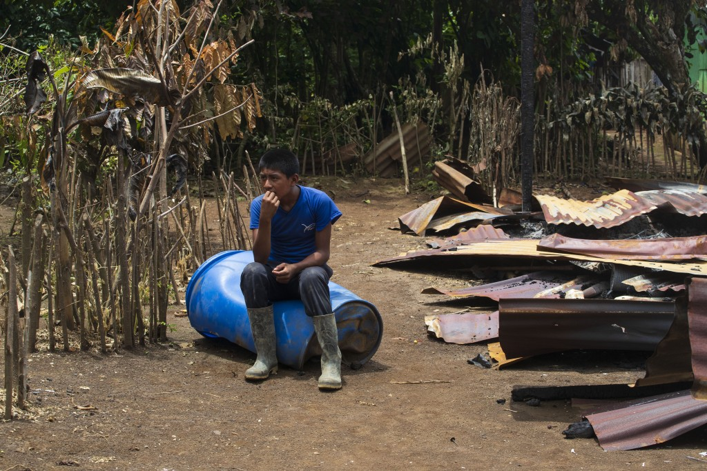 A youth sits next to his home after it was partially burned by unidentified, armed men, on a coffee plantation in Cubilguitz, Guatemala, Tuesday, Aug....