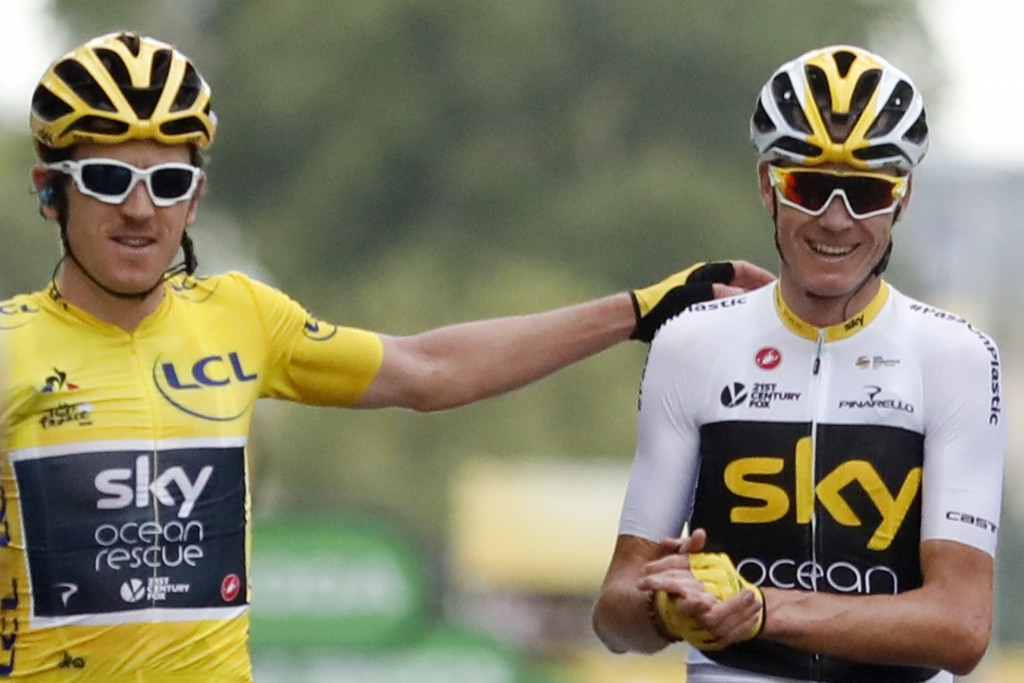 FILE - In this July 29, 2018 file photo, Tour de France winner Britain's Geraint Thomas, wearing the overall leader's yellow jersey, and Britain's Chr...