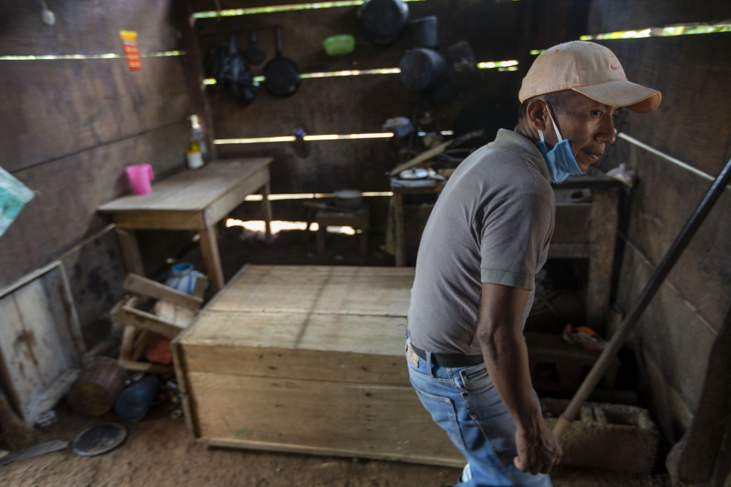 A man returns to his shack home after it was partially burned by unidentified, armed men, to see what remains where he lives on a coffee plantation in...