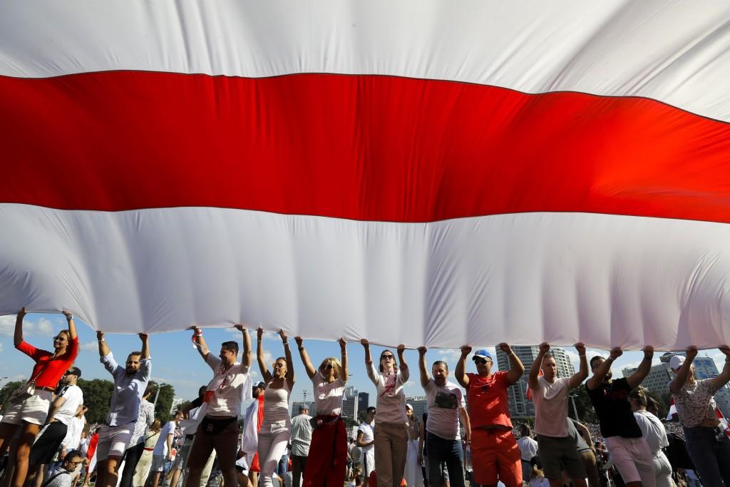 抗議民眾合舉大面國旗在街頭行進(美聯社圖片)。