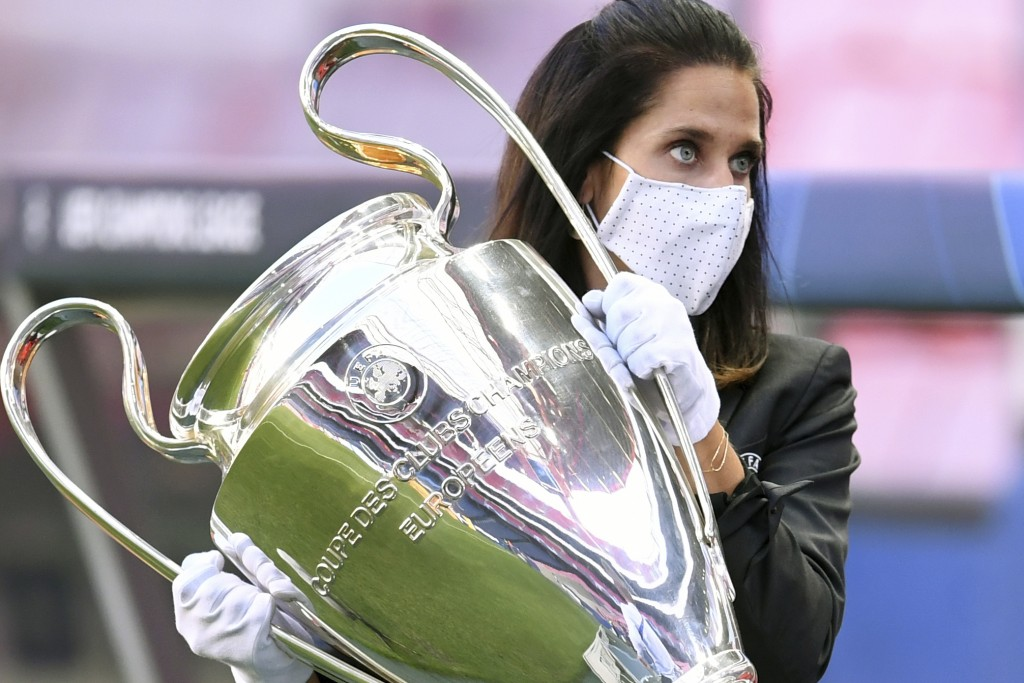 A member of the UEFA staff carries the Champions League trophy before the semifinal soccer match between RB Leipzig and Paris Saint-Germain at the Luz...