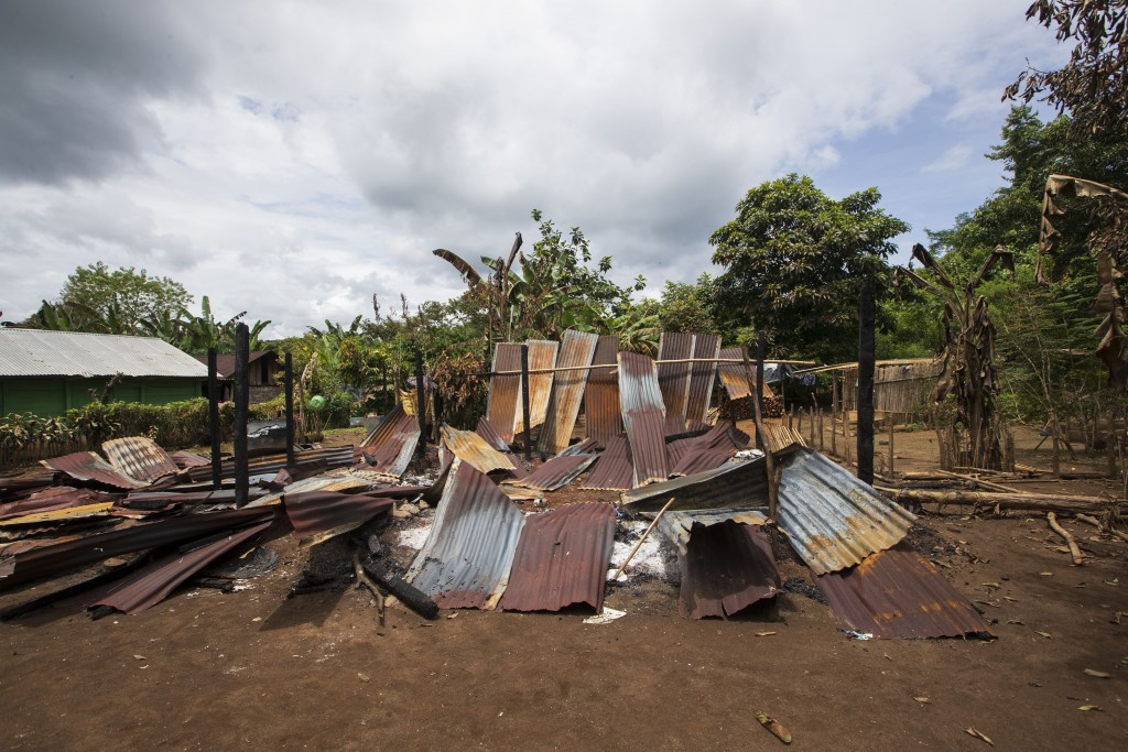 A shack home stands in ruins after it was burned by unidentified, armed men, as residents return to see what remains where they live on a coffee plant...