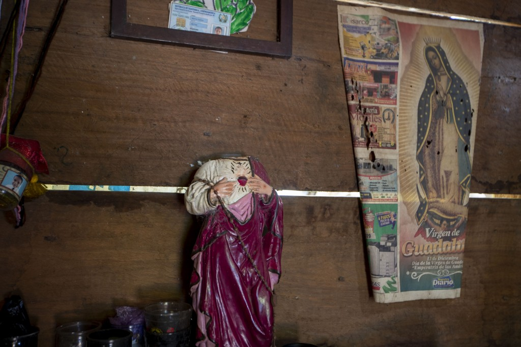 A statue of Jesus that was decapitated during an attack sits inside a home that was partially burned by unidentified, armed men, on a coffee plantatio...