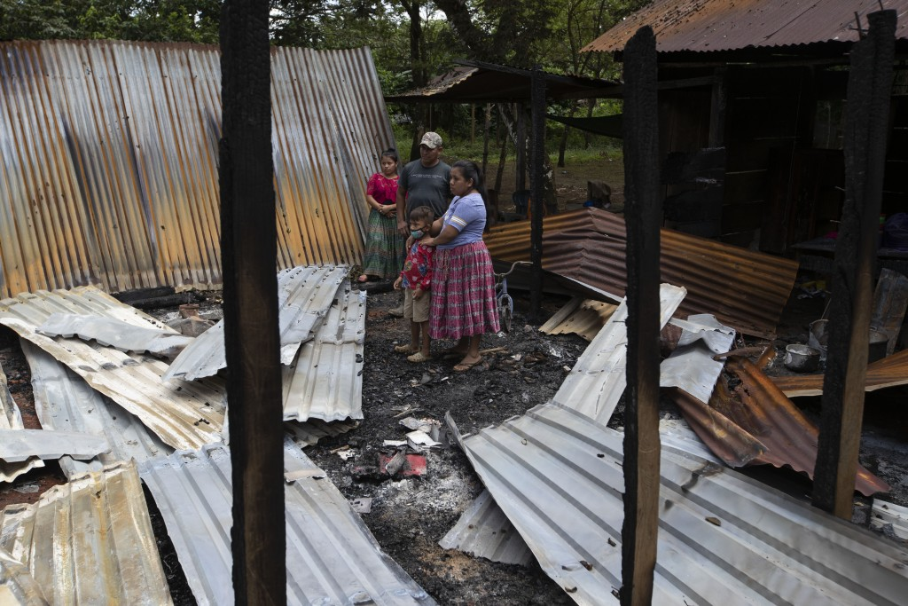 Floricelda Cucul, front right, stands with her husband Celestino Bol and children in the rubble of their shack home burned down by unidentified, armed...