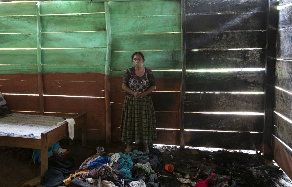 Ofelia Chuc Chuc, 50, stands inside her home after it was partially burned by unidentified, armed men, as she returns to see what remains where she li...
