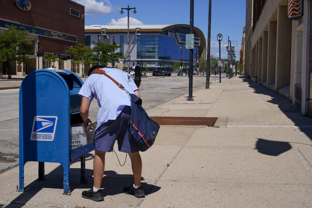 A postal worker empties a box near the Fiserv Forum on Tuesday, Aug. 18, 2020, in Milwaukee. With the Trump administration openly trying to undermine ...