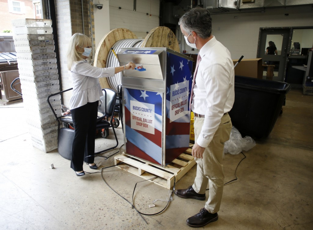 FILE - In this May 27, 2020, file photo, Bucks County commissioners Diane Ellis-Marseglia, left, and Robert Harvie unpack a new ballot drop box at the...