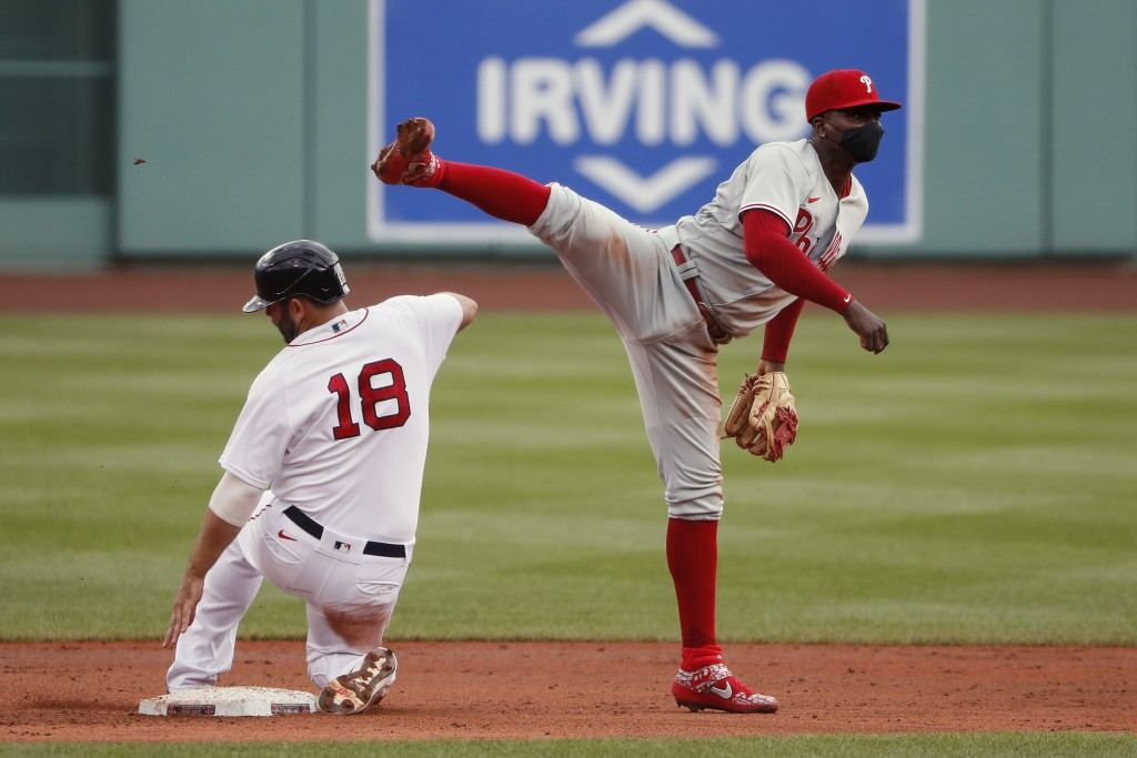 Philadelphia Phillies shortstop Didi Gregorius high steps over Boston Red Sox's Mitch Moreland to complete a double play in the second inning of a bas...