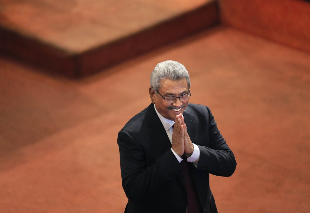 Sri Lankan President Gotabaya Rajapaksa greets ruling party lawmakers as he departs along the well of the parliament after delivering his policy speec...