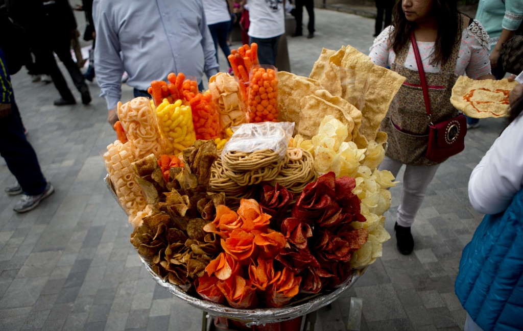 FILE - In this July 5, 2016 file photo, a street vendor sells fried snack food in Mexico City. As more states propose or approve bans on junk food sal...