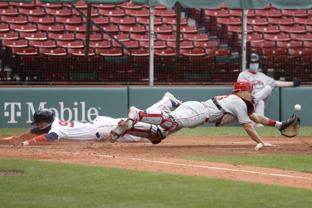 Philadelphia Phillies catcher J.T. Realmuto dives for the ball one way as Boston Red Sox's Alex Verdugo slides safely into home plate the other during...