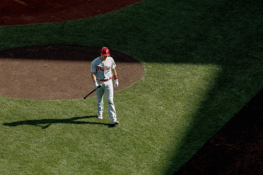 Philadelphia Phillies' J.T. Realmuto heads back to the dugout after striking out during the seventh inning of a baseball game against the Boston Red S...