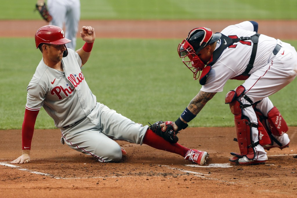 Philadelphia Phillies' Rhys Hoskins slides home safely ahead of the tag by Boston Red Sox catcher Christian Vazquez during the first inning of a baseb...