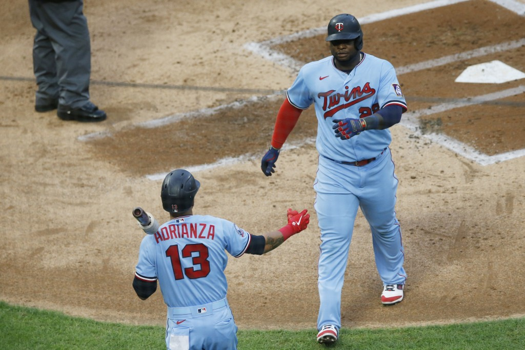Minnesota Twins' Miguel Sano, right, is congratulated by Ehire Adrianza after Sano scored on a single by Eddie Rosario off Milwaukee Brewers pitcher B...