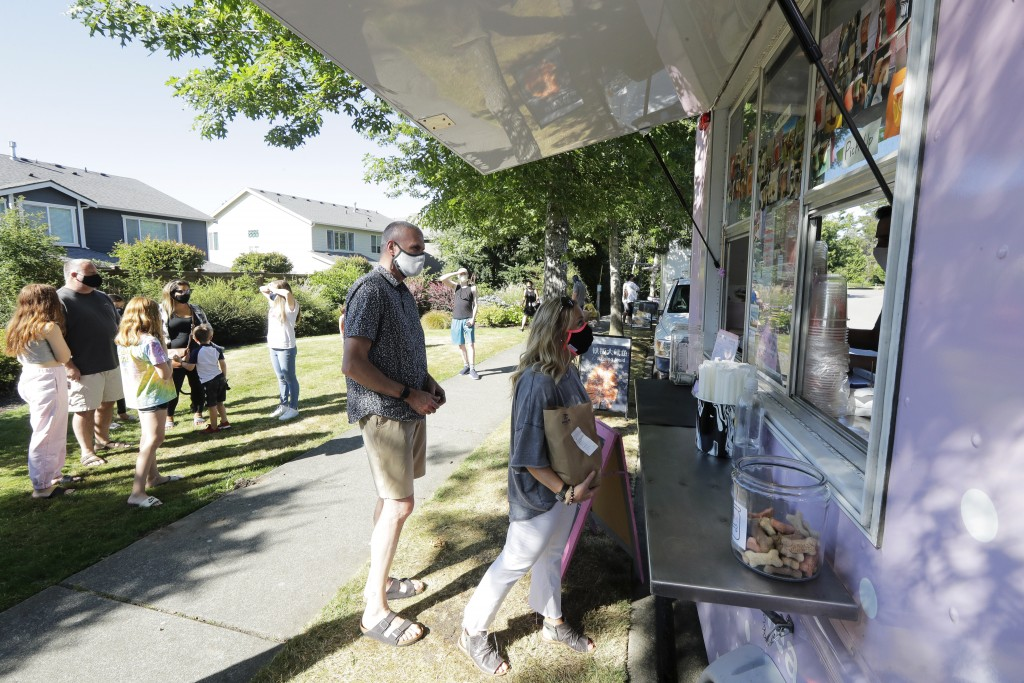 Julie and Greg Schwab wait to order from the Dreamy Drinks food truck, Monday, Aug. 10, 2020, near the suburb of Lynnwood, Wash., north of Seattle. In...