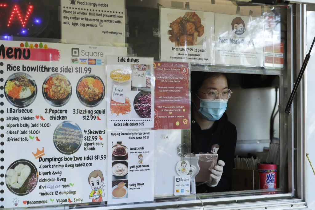 Yuli Shen takes an order as she works in her YS Street Food food truck, Monday, Aug. 10, 2020, near the suburb of Lynnwood, Wash., north of Seattle. L...