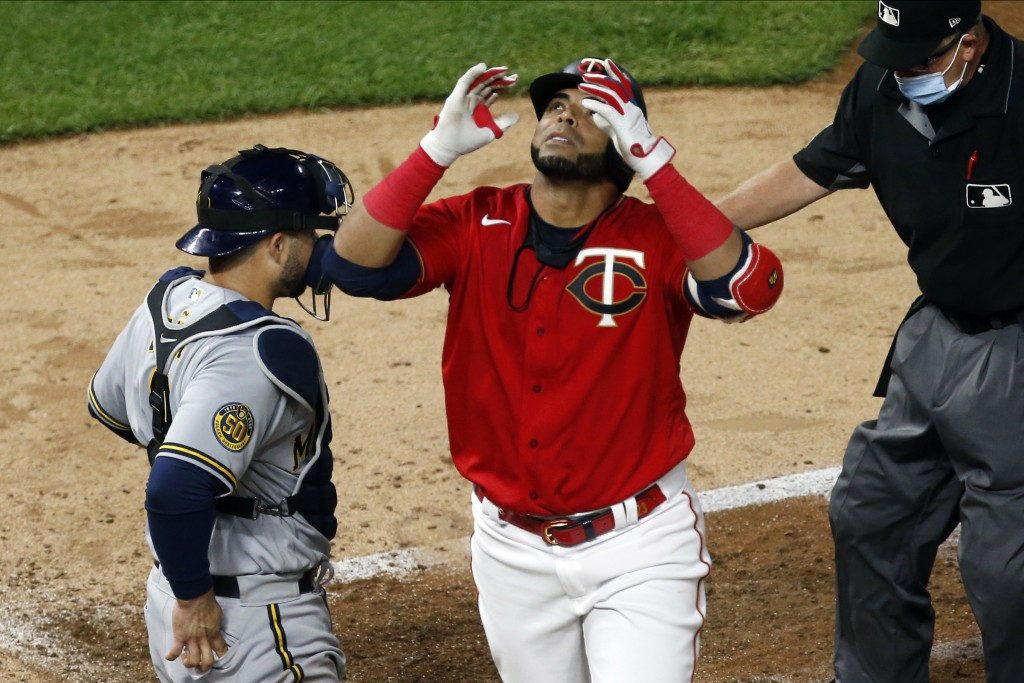 Minnesota Twins designated hitter Nelson Cruz looks skyward after hitting a two-run home run off Milwaukee Brewers' pitcher Freddy Peralta in the seve...