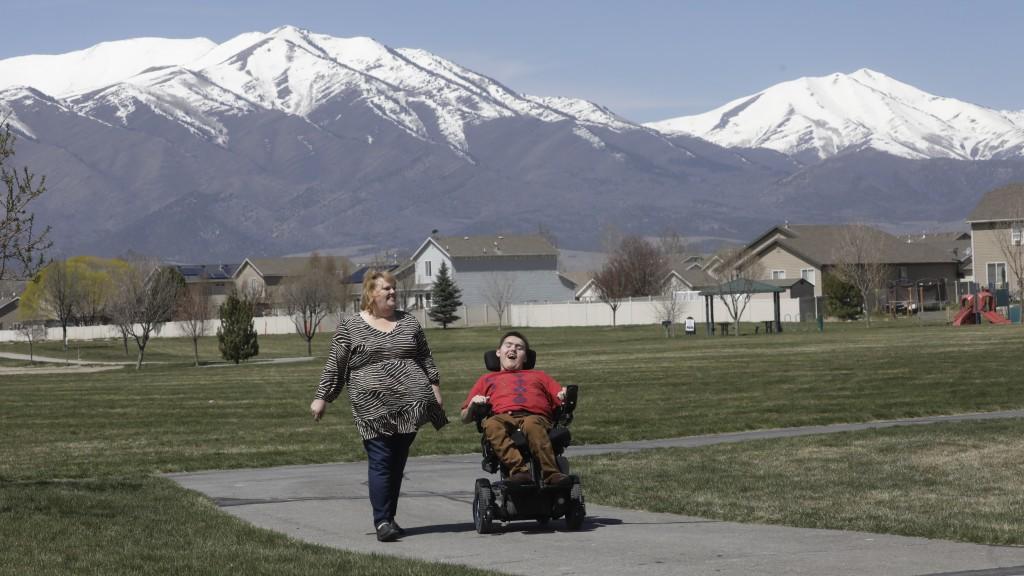 FILE - In this on April 14, 2020, file photo, Jodi Hansen walks with her son Jacob Hansen near their home in Eagle Mountain, Utah. Utah overhauled cri...
