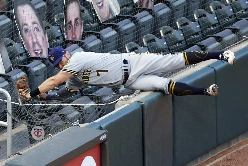 Milwaukee Brewers third baseman Eric Sogard gives over the fence and into the net to catch a foul ball off the bat of Minnesota Twins' Ehire Adrianza ...