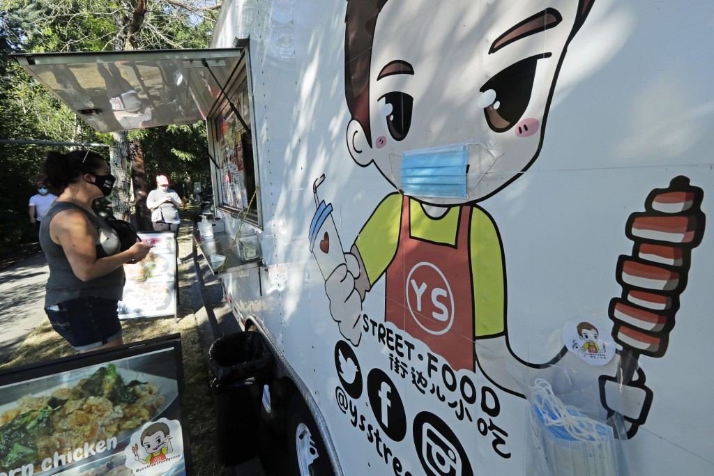A customer orders from the YS Street Food food truck, Monday, Aug. 10, 2020, near the suburb of Lynnwood, Wash., north of Seattle. Long seen as a feat...