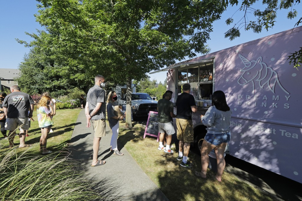 Customers line up to order from the Dreamy Drinks food truck, Monday, Aug. 10, 2020, near the suburb of Lynnwood, Wash., north of Seattle. Long seen a...