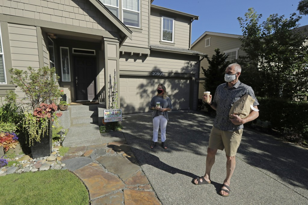 Julie and Greg Schwab stand in front of their home after walking back with their orders from the Dreamy Drinks and YS Street Food food trucks, Monday,...