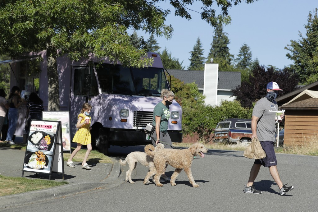 Bobby Price, right, and Catherine Vogt, center, walk with Catherine's daughter Avery, 8, and their dogs after ordering food and drinks from the YS Str...