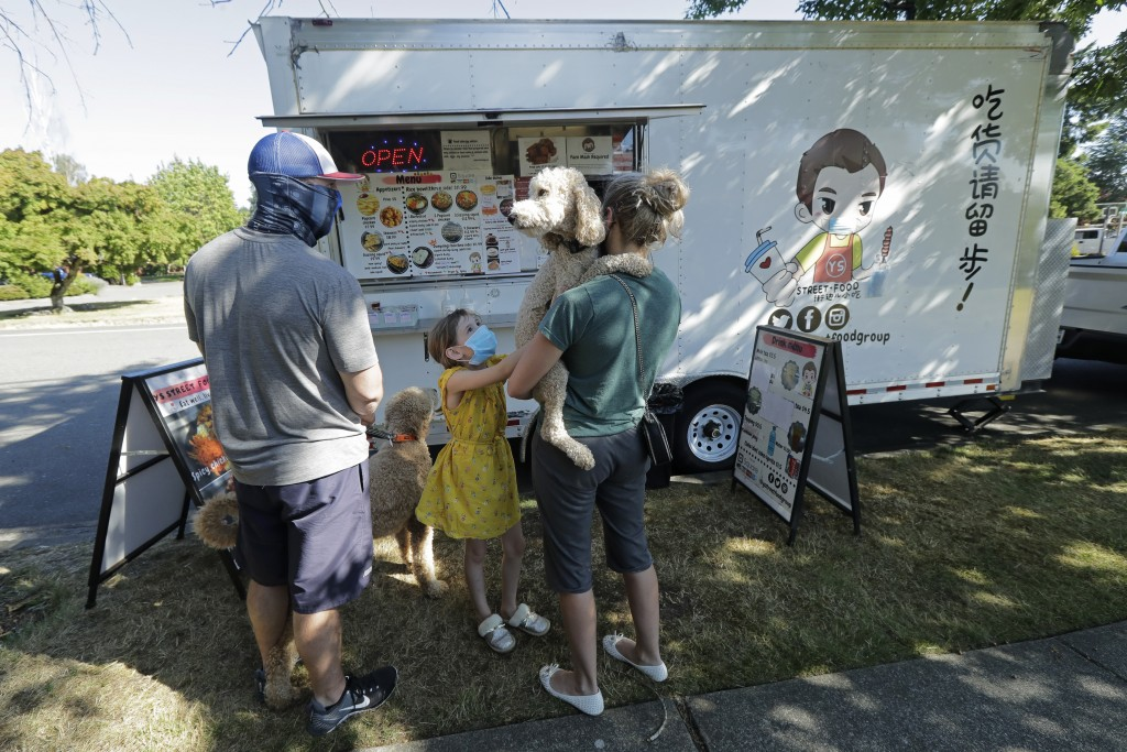 Bobby Price, left, and Catherine Vogt, right, stand with Catherine's daughter Avery, 8, and their dogs as they wait to order from the YS Street Food f...