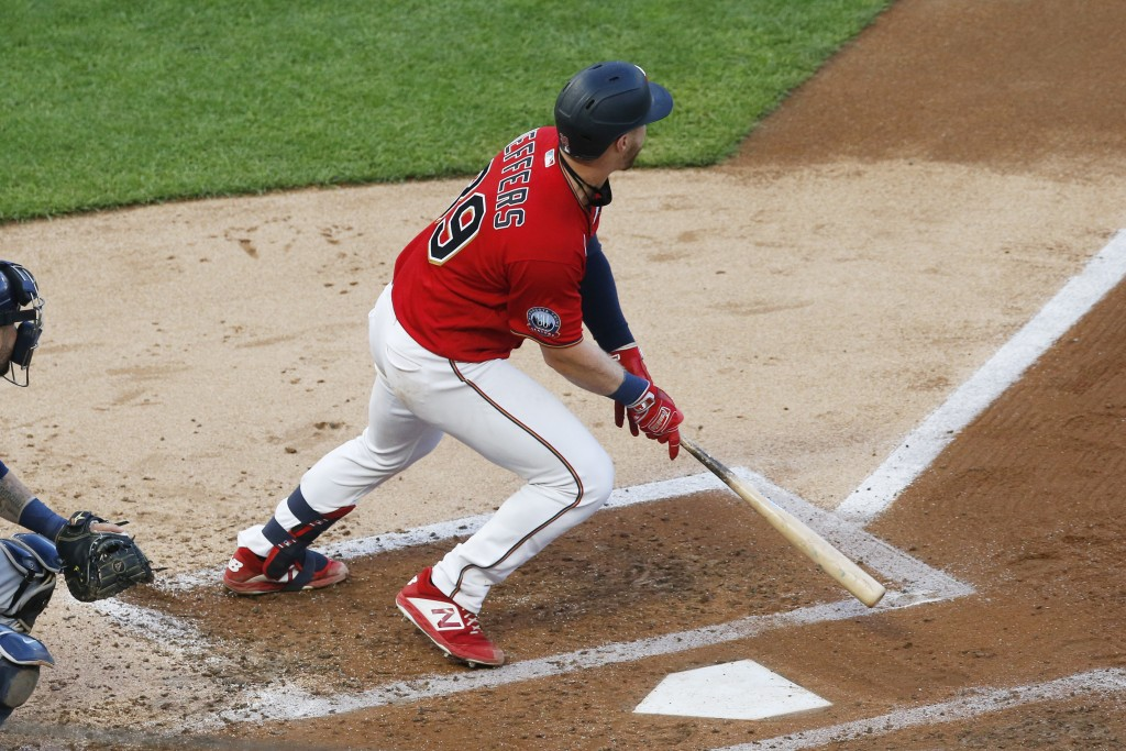 Minnesota Twins' Ryan Jeffers hits an RBI single off Milwaukee Brewers pitcher Brandon Woodruff in the third inning of a baseball game Thursday, Aug. ...