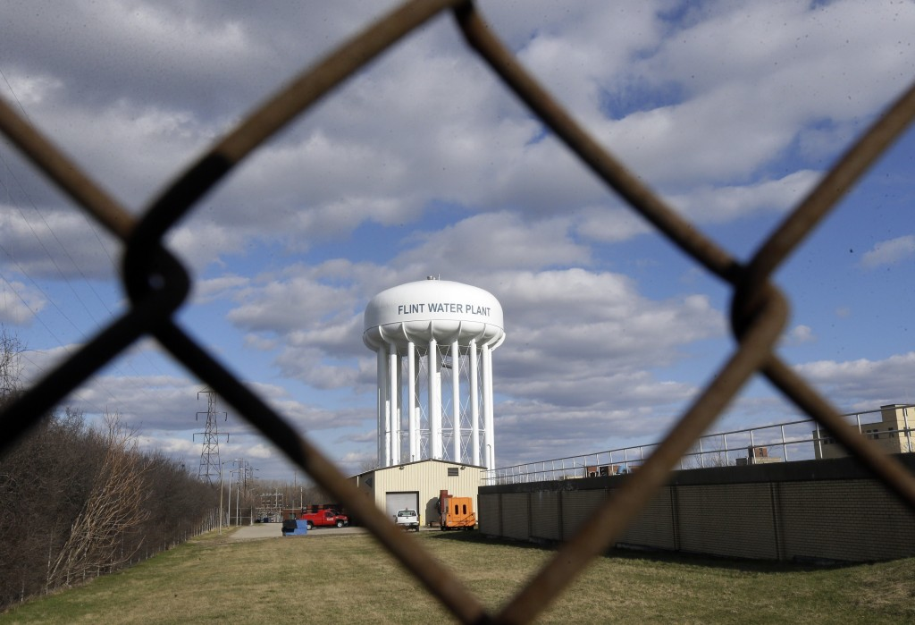 FIL - In this March 21, 2016, file photo the Flint Water Plant water tower is seen in Flint, Mich. Michigan Gov. Gretchen Whitmer says a proposed $600...