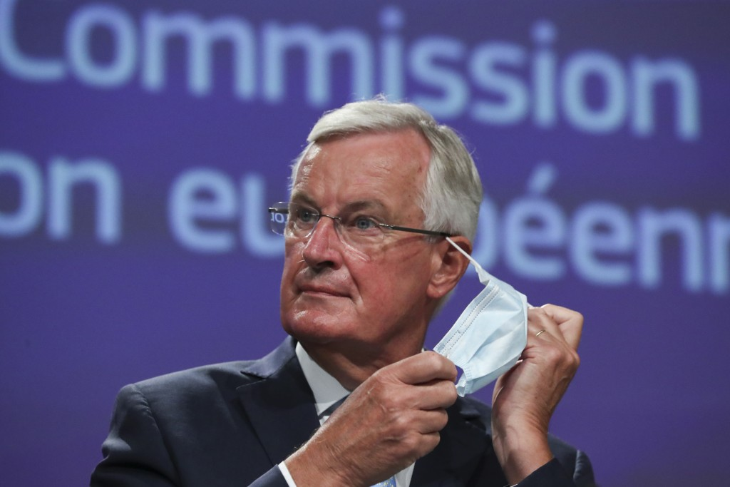 European Union chief Brexit negotiator Michel Barnier takes off his protective face mask prior to speaking at a media conference after Brexit trade ta...