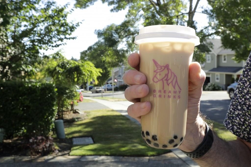 Greg Schwab holds a boba tea he ordered from the Dreamy Drinks food truck, Monday, Aug. 10, 2020, near the suburb of Lynnwood, Wash., north of Seattle...