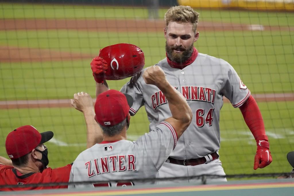 Cincinnati Reds' Matt Davidson (64) is congratulated by hitting coach Alan Zinter after hitting a grand slam during the sixth inning of a baseball gam...