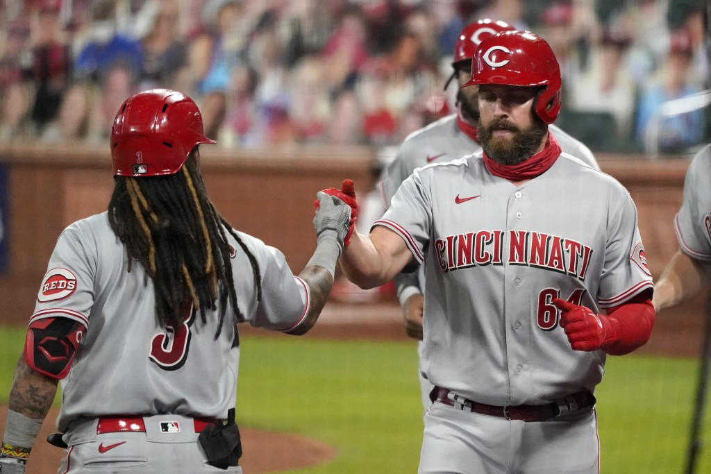Cincinnati Reds' Matt Davidson (64) is congratulated by teammate Freddy Galvis after hitting a grand slam during the sixth inning of a baseball game a...