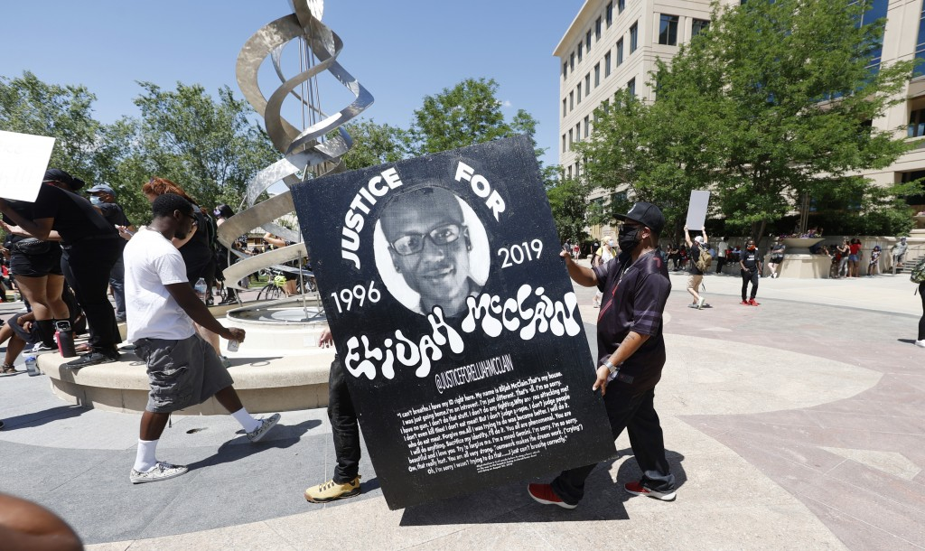 FILE - In this June 27, 2020, file photo, demonstrators carry a giant placard during a rally and march over the death of 23-year-old Elijah McClain ou...