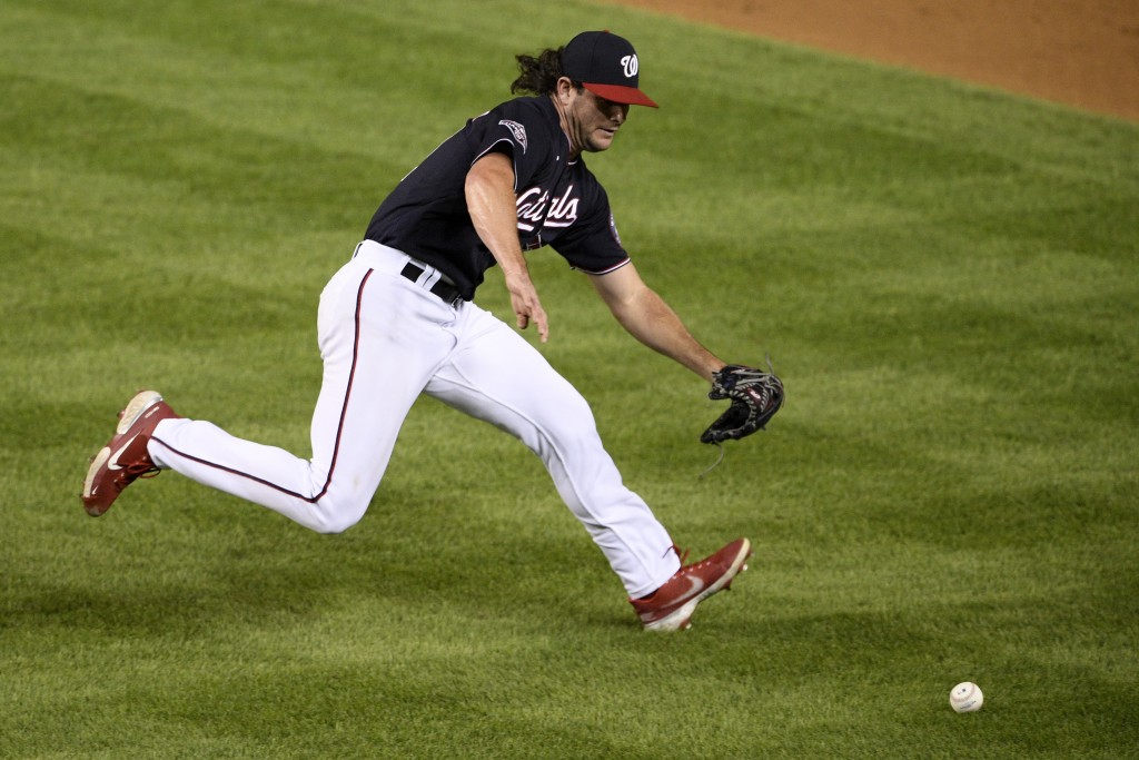 Washington Nationals relief pitcher Kyle Finnegan chases a ground ball by Miami Marlins' Jonathan Villar during the ninth inning of a baseball game, F...