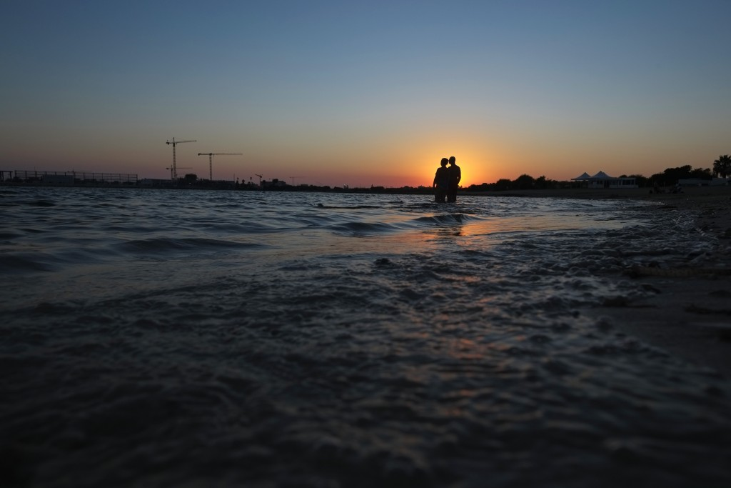 A couple stand in the sea during sunset in coastal resort of Ayia Napa in the eastern Mediterranean island of Cyprus, Saturday, Aug. 22, 2020.  Meanwh...