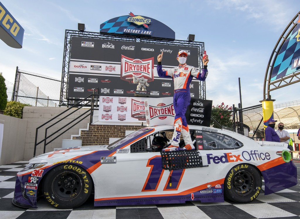 Denny Hamlin stands on his car after winning the NASCAR Cup Series auto race at Dover International Speedway, Saturday, Aug. 22, 2020, in Dover, Del. ...