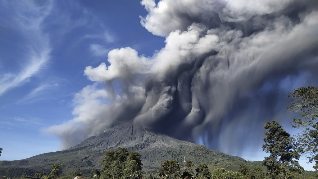 Mount Sinabung spews volcanic materials during an eruption, in Karo, North Sumatra, Indonesia, Sunday, Aug. 23, 2020. Sinabung is among more than 120 ...