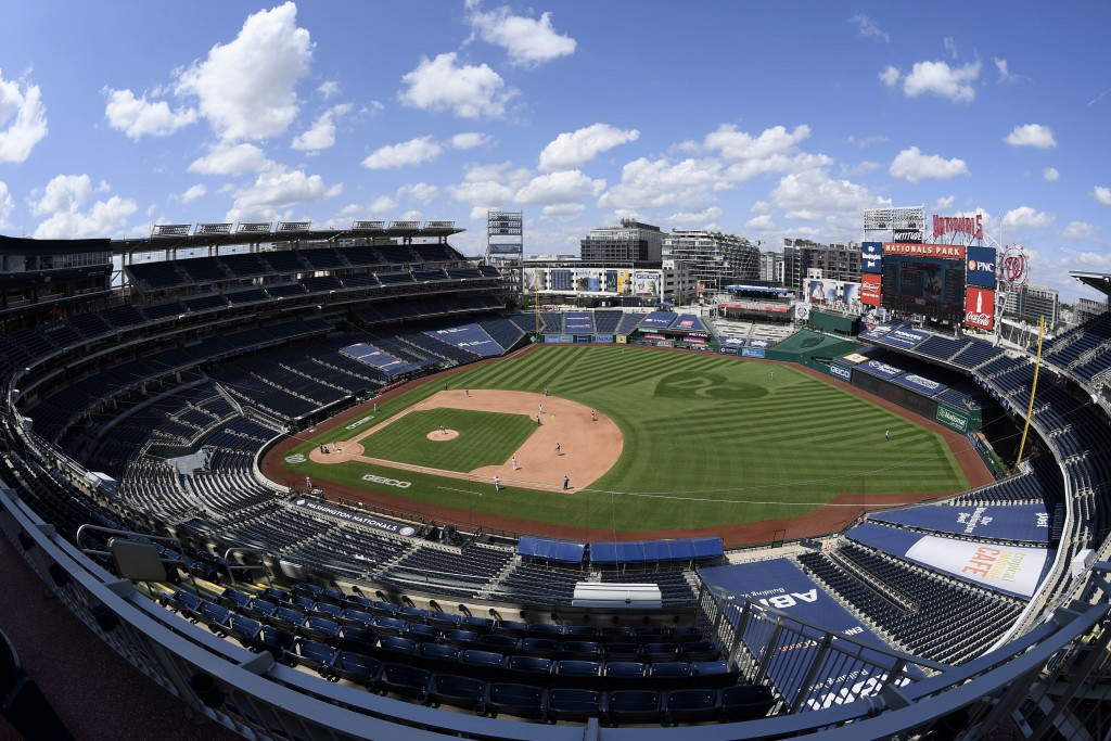 In this photograph taken with a fisheye lens, the Washington Nationals and the Miami Marlins compete during the fourth inning of a baseball game, Sund...