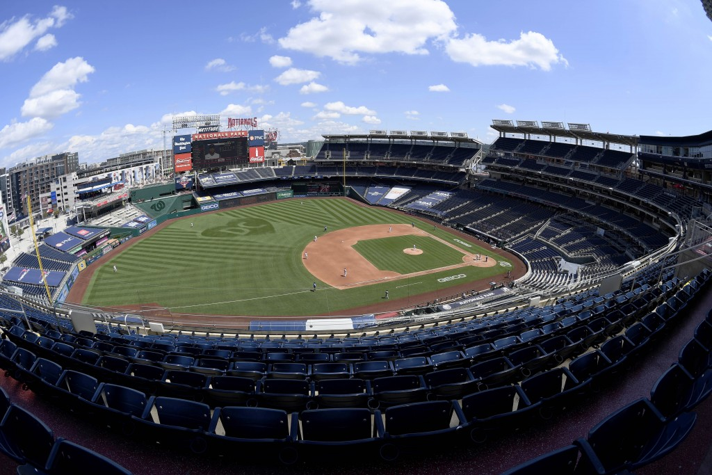 In this photograph taken with a fisheye lens, the Washington Nationals and the Miami Marlinsm compete during the fourth inning of a baseball game, Sun...
