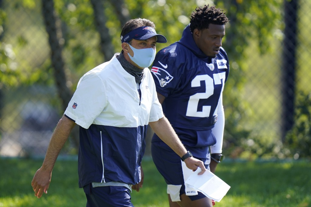 New England Patriots quarterback coach Jedd Fisch, left, and defensive back J.C. Jackson, right, step on the field at the start of an NFL football tra...