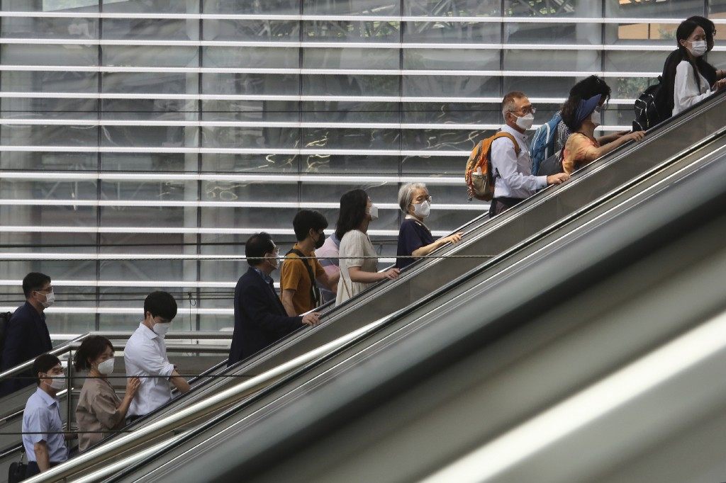 People wearing face masks to help protect against the spread of the coronavirus ride an escalator as they arrive at the Seoul Railway Station in Seoul...